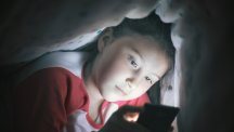 Child playing tablet in dark T