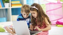 Boy and girl playing laptop