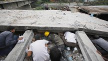 Rescuers look for victims under a collapsed building in Kathmandu (AP)