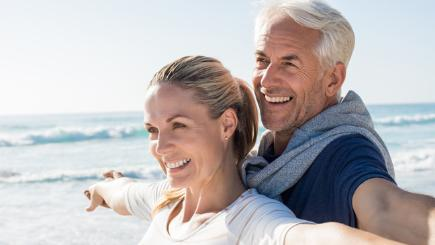 Older couple by the beach looking happy