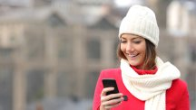 Woman in scarf and hat looking at phone TS