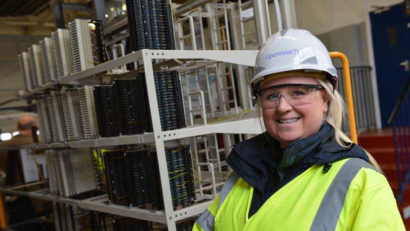 Woman engineer near servers to Openreach hat on
