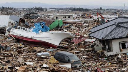 A fishing boat sits amongst debris of houses and cars in Natori, Miyagi Prefecture, Japan