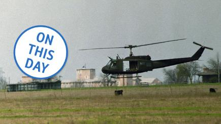 A helicopter hovers near the Branch Davidian compound in Waco, Texas
