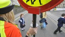 A lollipop lady shows children and a parent safely across a street.