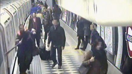 A member of staff pursuing a passenger and their scarf which was trapped in tube train doors, as the train departs from the platform