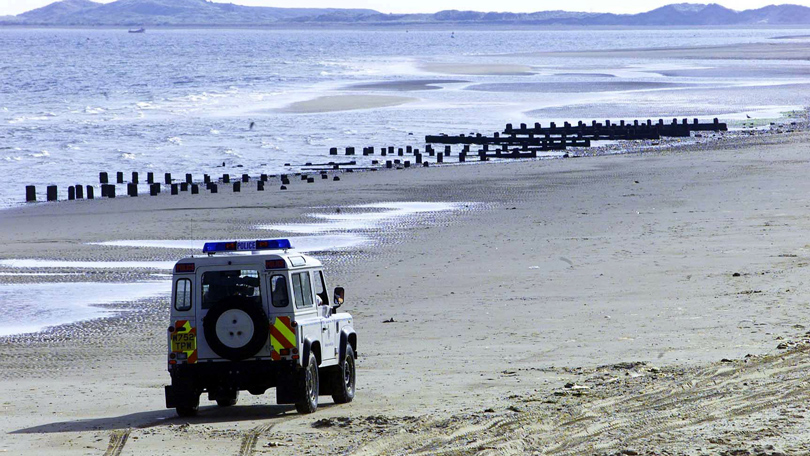 A Police Land Rover driving on Brancaster beach