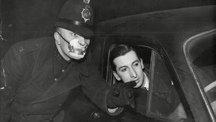 A policeman wearing a smog mask directs a car driver.