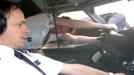 A reconstruction of pilot Tim Lancaster's legs being held by a flight attendant (Image credit: National Geographic Channel).