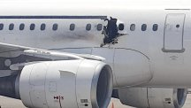 A hole in a plane operated by Daallo Airlines as it sits on the runway of the airport in Mogadishu, Somalia. (AP)