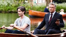 Alec Baldwin in a boat, using a BT Mobile phone, while another man rows