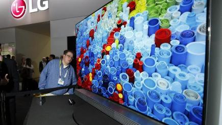 "Brian Benson eyes the slim depth of the LG 65"" 4K ULTRA HD OLED TV at the 2015 International CES (Photo by Jack Dempsey/Invision for LG/AP Images)"