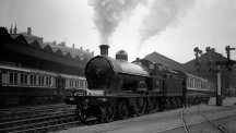 An oil-fired steam locomotive on the London and North Western Railway leaving Euston Station, London.