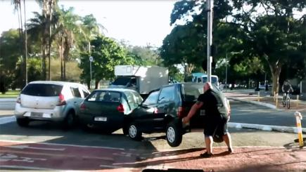 Screengrab of man lifting a motor car out of a cycle lane with his bare hands. Photo credit: Joe Loreto