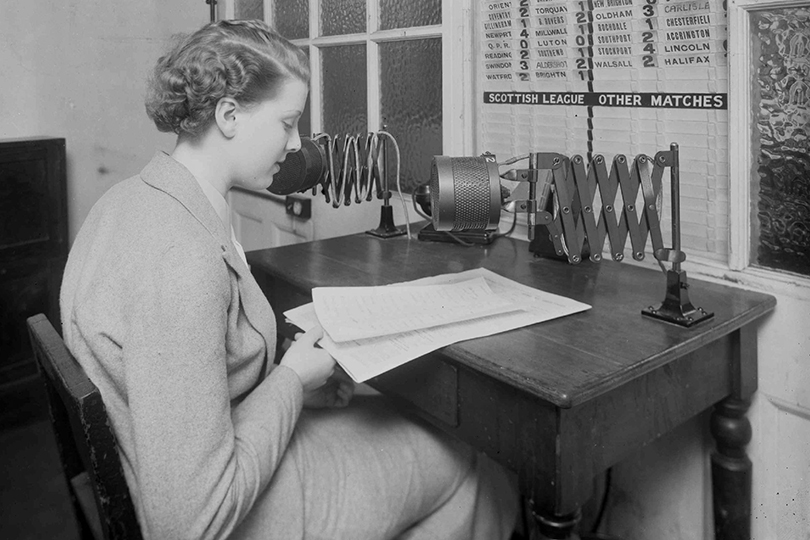 Announcer at the microphone during a newspaper telephone sports broadcast. 1936.