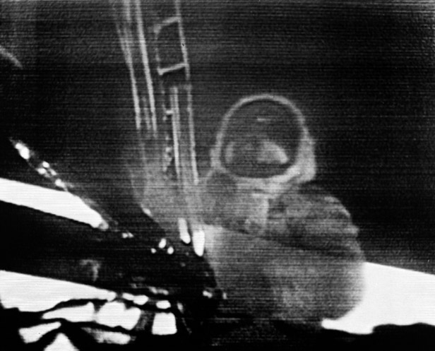 Neil Armstrong climbs off Eagle's bottom step to set foot on the Moon.
