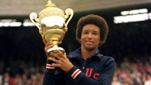 Arthur Ashe lifts the Wimbledon trophy after becoming the first black man to win the Men's Singles in 1975.