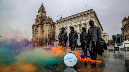 Smoke flares are set off next to the Beatles statue on Liverpool's waterfront to launch Sgt Pepper at 50: Heading For Home