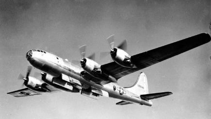 Black and white B-29 Superfortress plane flying in sky