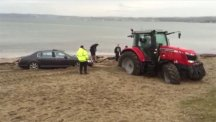 Screengrab of a Bentley being rescued from a Cornish beach by a tractor.  Photo credit: SWNS