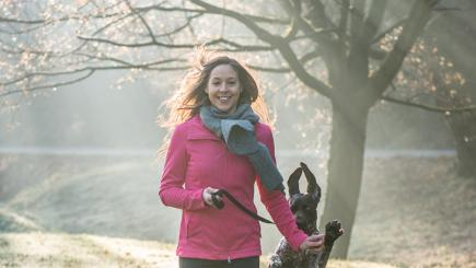 Woman in pink top running in cold with dog