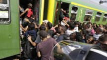 Refugees try to board a train in Bicske, Hungary (AP)