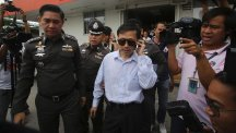 Doctor Sompob Sansiri is escorted by Thai police officers at a police station following his arrest in Bangkok