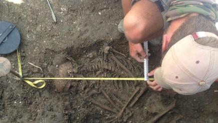 A rare Bronze Age skeleton has been found by archaeologists excavating Wilsford henge in the Vale of Pewsey, Wiltshire (University of Reading/PA)