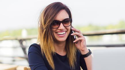 A woman in sunglasses laughs while using her mobile phone