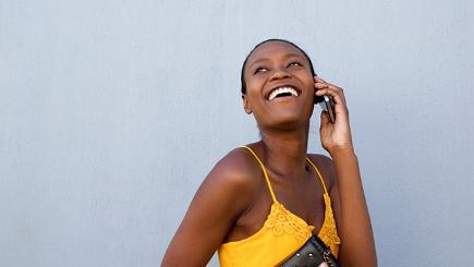 A woman smiles and looks upwards while using her mobile phone against a grey wall