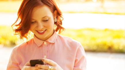 A smiling young woman with red hair using a mobile phone with the sun in the background