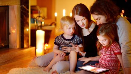 Family by fire with tablet