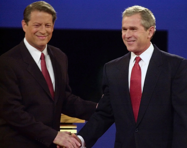 Candiates Al Gore and George W. Bush shake hands at a televised debate.