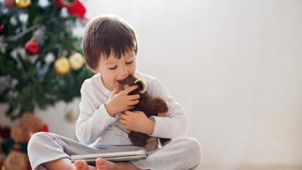 Child using tablet by Christmas tree