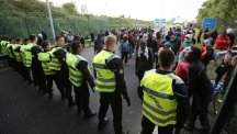 Migrants face a police cordon by the perimeter fence of the Eurotunnel site at Coquelles in Calais, France