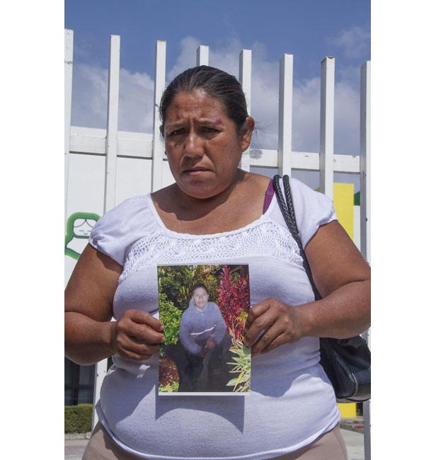 Rosalia Diaz Cueto, mother of Ezekiel Cordoba, holds a photo of her dead son.