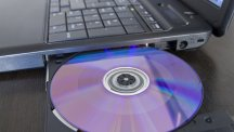 CD being inserted into laptop