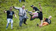 Participants tumble after the Double Gloucester cheese as it hurtles down Coopers Hill, Gloucestershire, in the annual Cheese Rolling competition, which is being held unofficially this year. (PA)