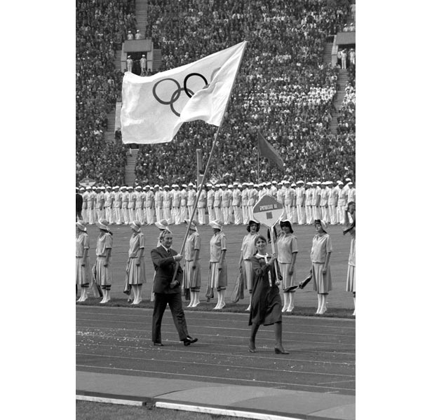 Dick Palmer, Great Britain's Chef de Mission at the Moscow Games, is the country's sole representative at the opening ceremony and carries the Olympic flag instead of the Union Jack.