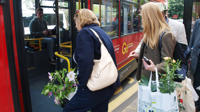 Passengers board a bus as they leave the RHS Chelsea Flower Show loaded down with flowers