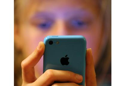 Child staring at blue phone