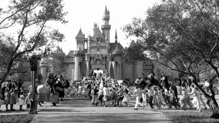 Children sprint across a drawbridge and into the castle that marks the entrance to Fantasyland at the opening of Walt Disney's Disneyland.
