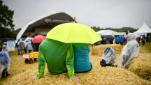 People sit under brollies to keep out of the Bank Holiday rain at the Big Festival in Oxfordshire