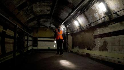 A man walks along a passenger tunnel in the disused Down Street station in London's Mayfair district