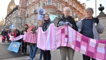 Protesters hold a scarf during a CND march against Trident nuclear missiles in London. The pink-coloured scarf, knitted by people across the world, encircled the Ministry of Defence building in central London as part of the demonstration. (PA)