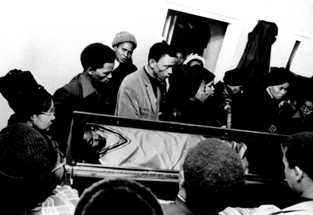 Mourners surround Biko's coffin in his home in the black township of Ginsberg, South Africa. A mirror on the raised lid of the coffin reflects the gold-robed body.