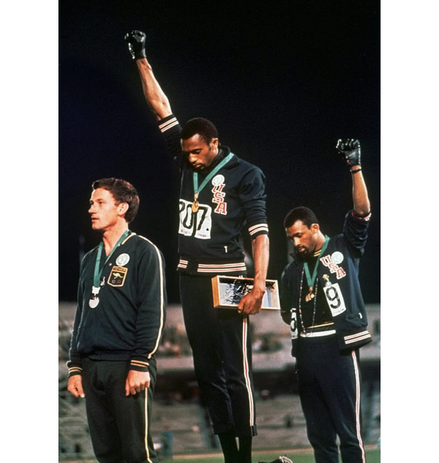 Smith (centre) and Carlos (right) give the salute while Norman (front) wore the badge of the Olympic Project for Human Rights.