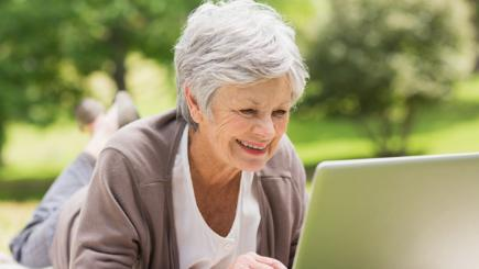 Older woman using laptop in park