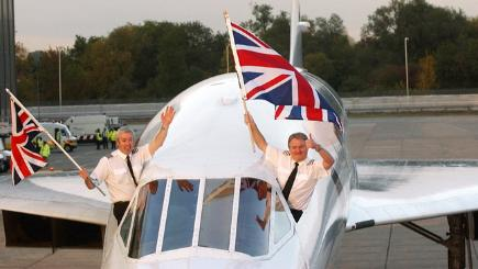 Concorde's pilot and co-pilot wave the Union Flag on arrival at Heathrow.