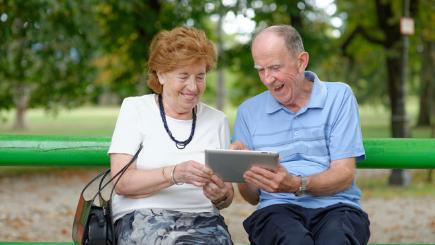 Couple with iPad on bench